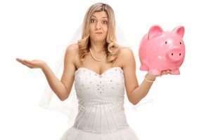 Bride holding piggy bank shrugging