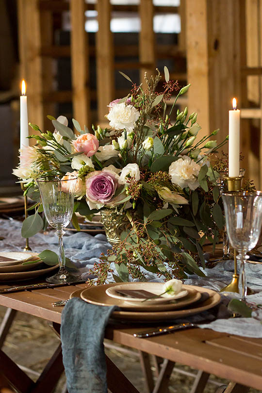 A wedding place setting in a rustic barn